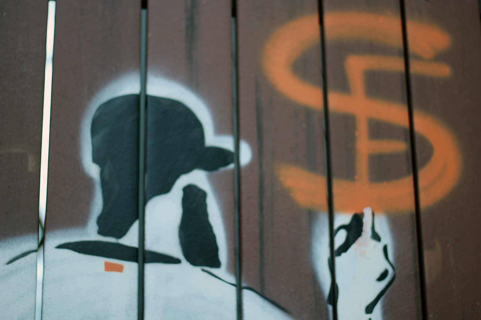 A mural on a fence door shows pitcher Brian Wilson painting the San Francisco Giants symbol.