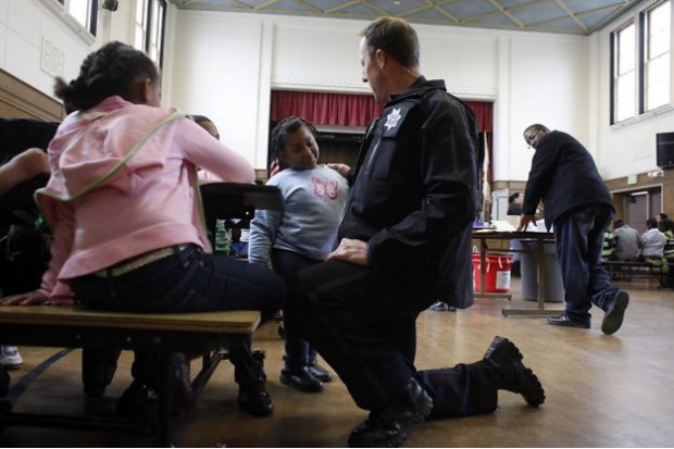 Officer Rick Moore talks to students at Oakland's Piedmont Elementary School. Photo courtesy of The San Francisco Chronicle
