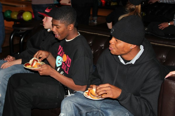 The teenagers enjoy food as they bowl.