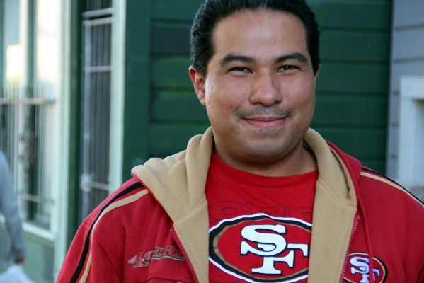 """Nelson Arias dons his 49ers gear as he walks on 23rd Street. Simply put, the 49ers will win """"because we're better,"""" he says."""