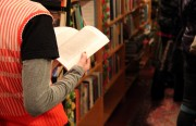 """A young woman flips through a book on the night of """"A Celebration of the Adobe Bookshop."""" Photo by Molly Oleson"""