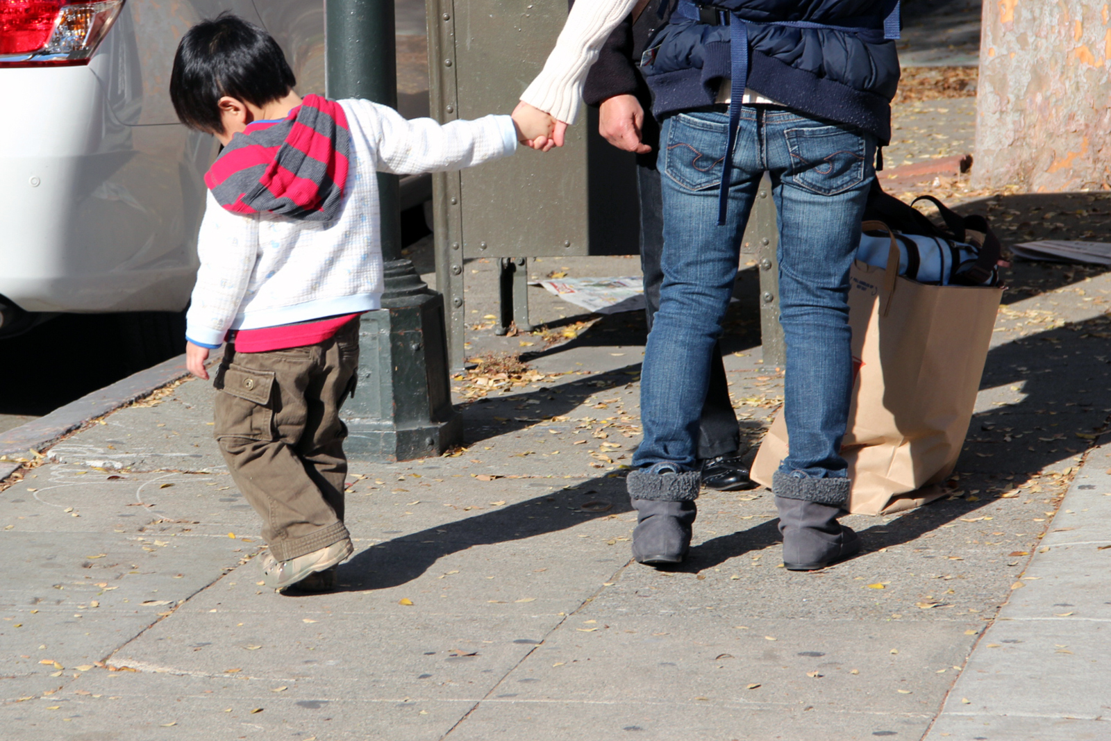 A boy holds his mom's hand on Folsom Street.