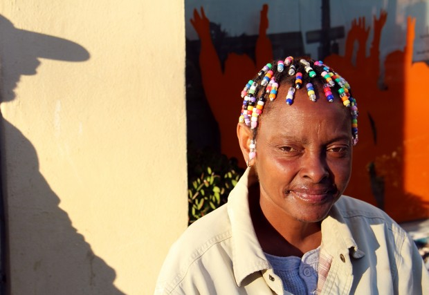 A woman with colorful beads in her hair soaks up the sun on 16th Street.