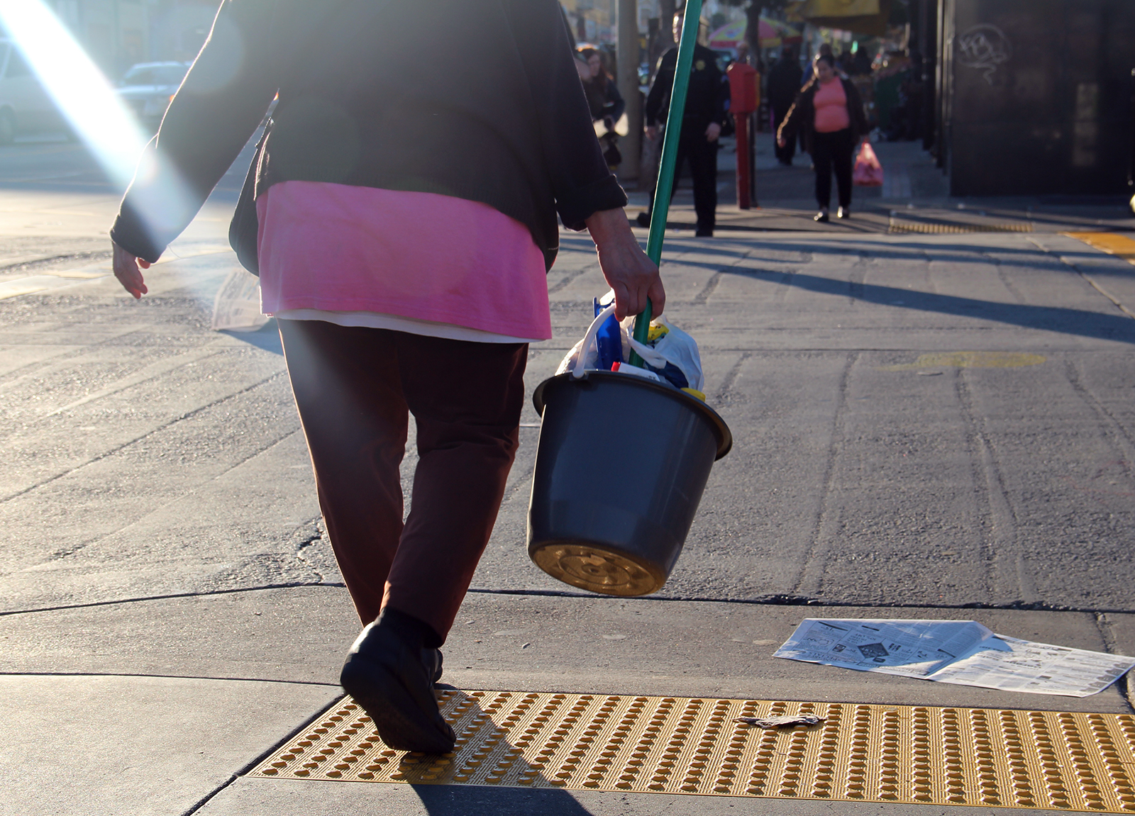 A woman crosses Mission Street with a bucket full of cleaning supplies.