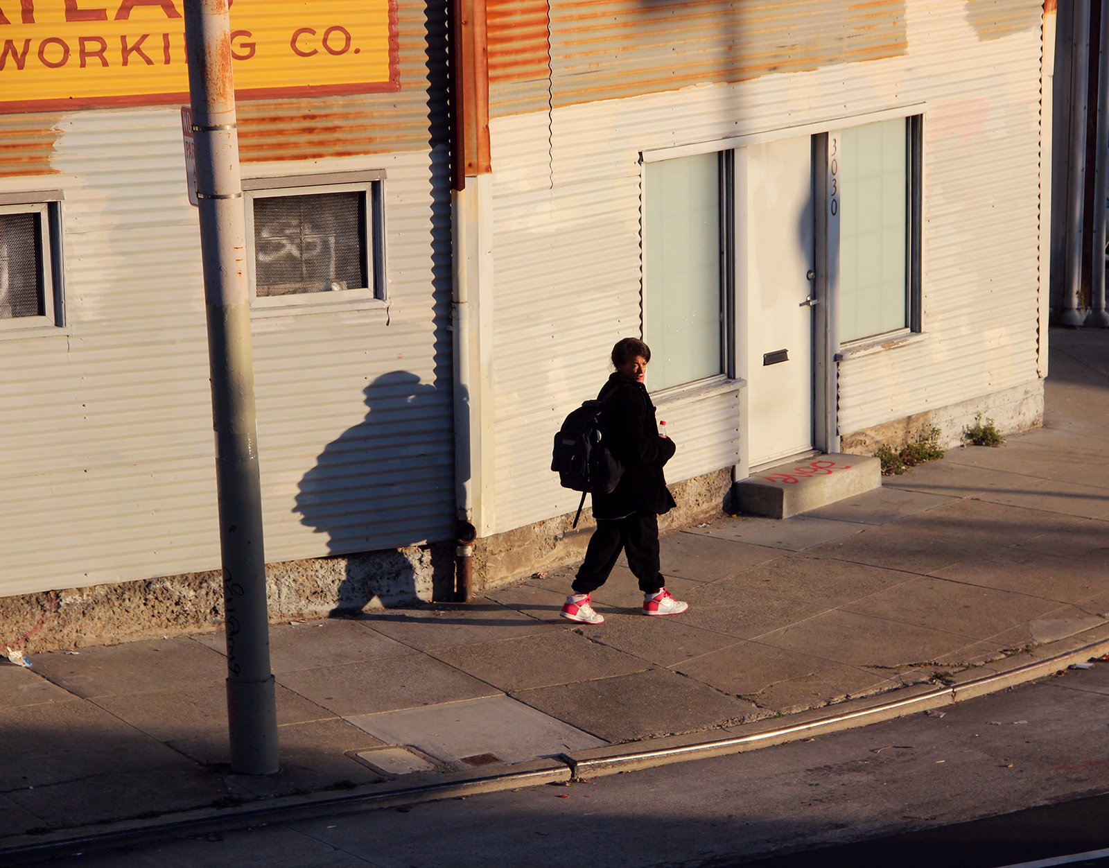 A woman rounds the corner on 17th Street as the sun sets.