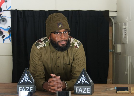 Johnny Travis wears a Faze button-down shirt and army green beanie.