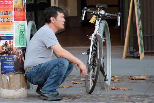 A man takes a cigarette break on Valencia Street.