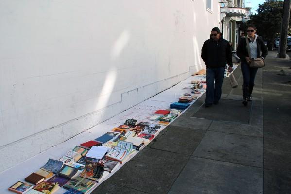 People walk by a street book sale.