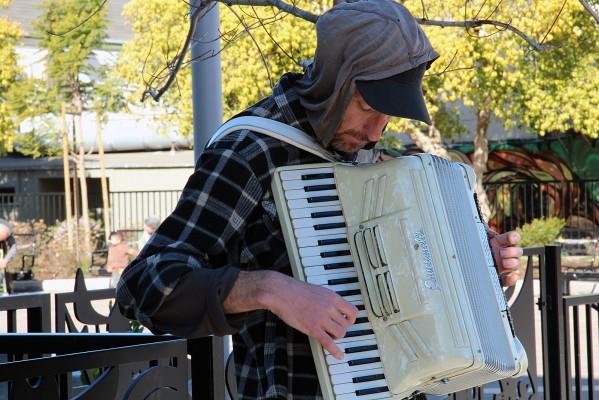 A man plays an accordion on Valencia Street.