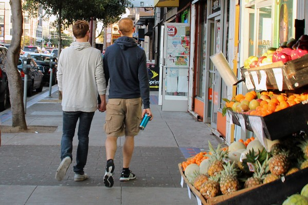 Two men hold hands as they walk down Mission Street.