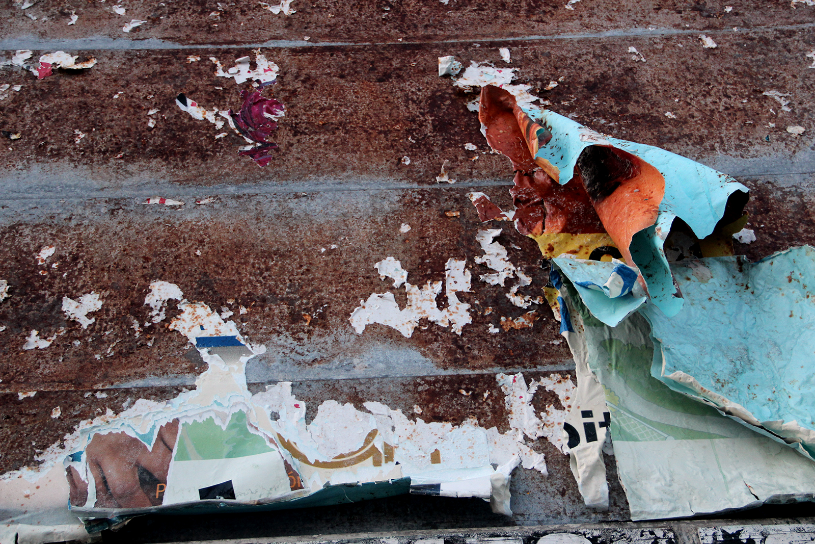 A ripped sign remains on a board, with clues of what used to be.