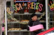 A man carries a Rosca De Rey outside Panaderia La Mexicana.