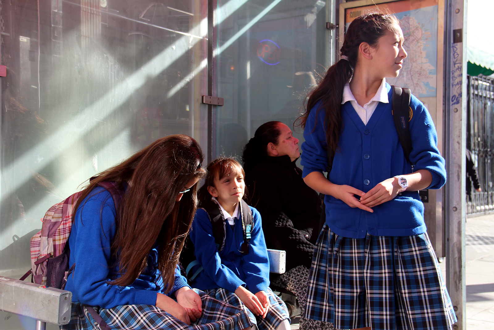Young girls wait for the bus on Mission Street.