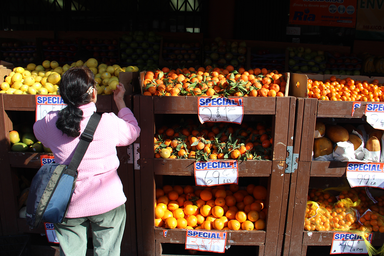 A woman selects fruit on mission Street.