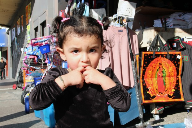 A young girl with her fingers in her mouth on Mission St. near 22nd St.