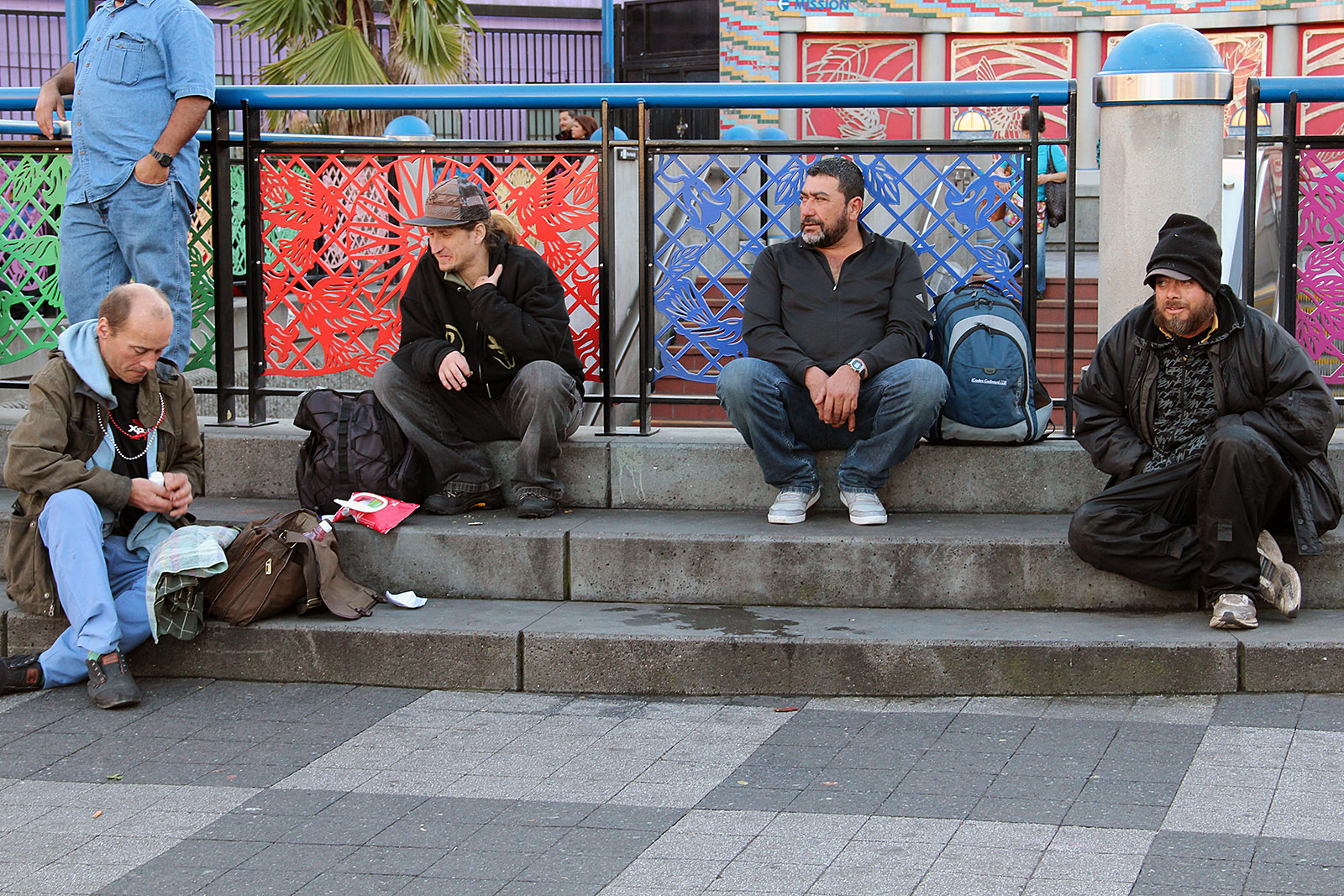 A group of men sit outside the 16th Street Bart Station.