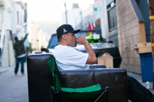 Man drinks from a bottle while watching game in street