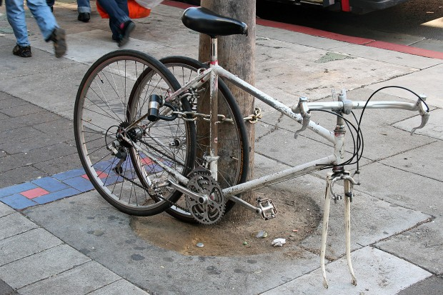 A bicycle on Mission Street is missing a wheel.