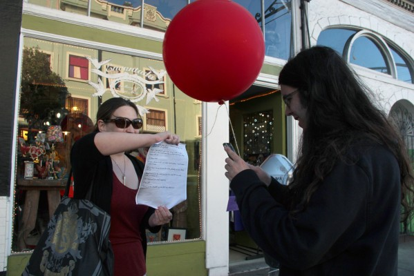 Charissa Faire holds a love letter while Julian Maestas scans it on his phone to save to his digital archive of found letters.