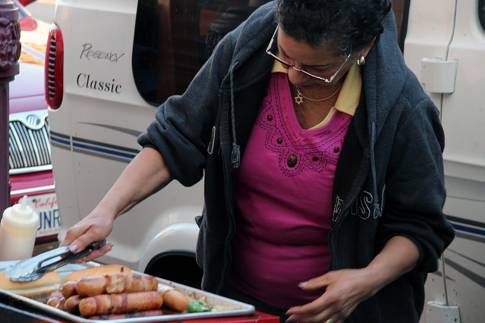 A woman makes hot dogs on Mission Street.