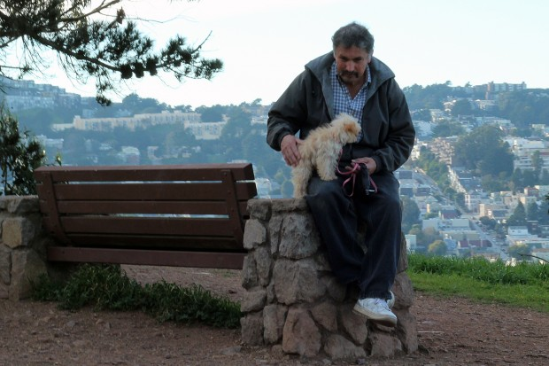 A man sits with his dog as he looks out over the Mission from Bernal Hill.