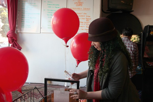 Olga Nunes taking down balloons at Lost Weekend the day after the scavenger hunt