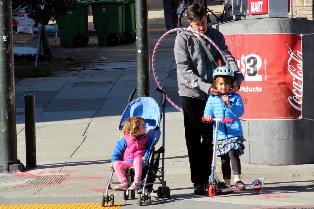 A dad walks with his daughters near Valencia and 24th streets.