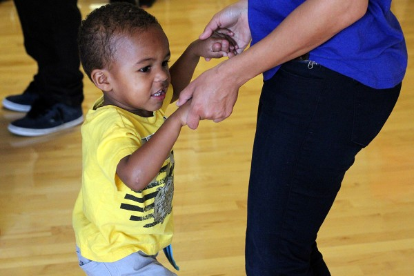 "A child dances with his mother at Loco Bloco's ""Hella Loco Carnaval"" classes Saturday."