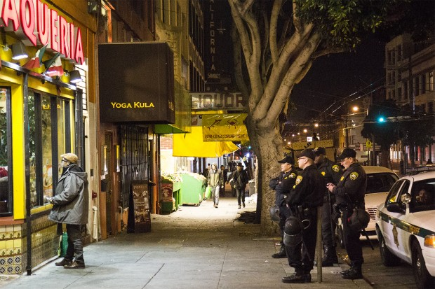 Police officers watch the end of the game through the window of Taqueria Los Coyotes on 16th Street. (Photo by Marta Franco)