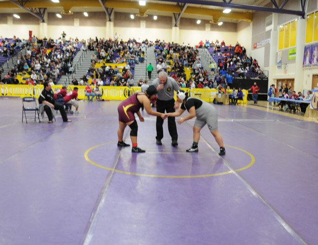 Jazmine Chavarria from West Covina High School and Marlyn Martinez wrestle in Lemoore Calif. at the girls' state championships.