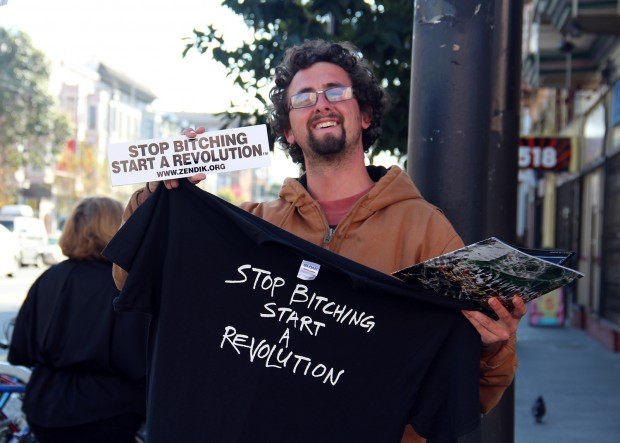 A man stands on Valencia Street advertising a group he hopes people will join.