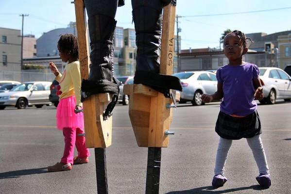 una niña viendo cómo se usan los zancos.