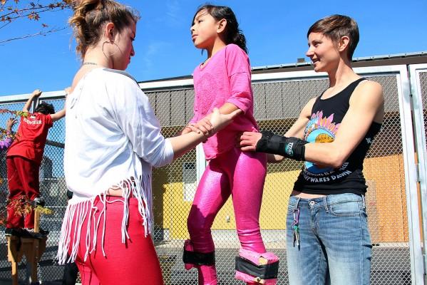 Una niña practicando cómo caminar en zancos en la clase que ofrece Loco Bloco para el carnaval.