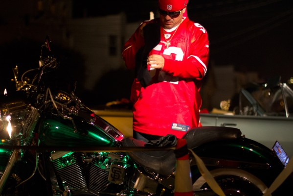 """A 49ers fan prepares to ride away from the """"Frisco's Finest Car Club"""" block party. (Photo by Lauren Kate Rosenblum)"""