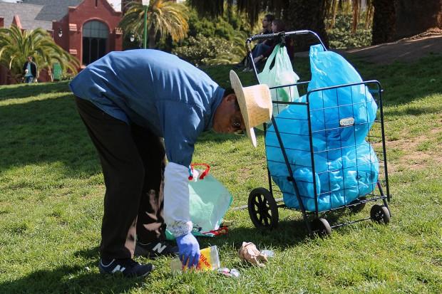 A man cleans up trash at Dolores Park.
