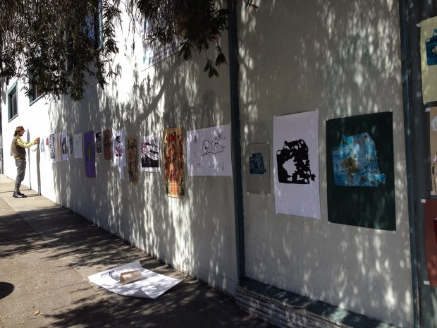 A man hangs art on Valencia Street.
