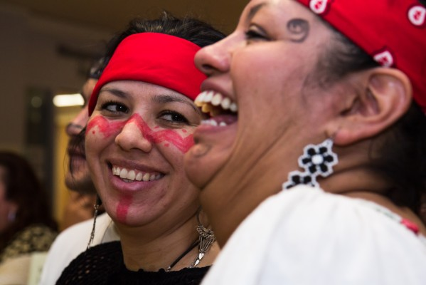 Two women laugh during the ceremony at the CCSF.
