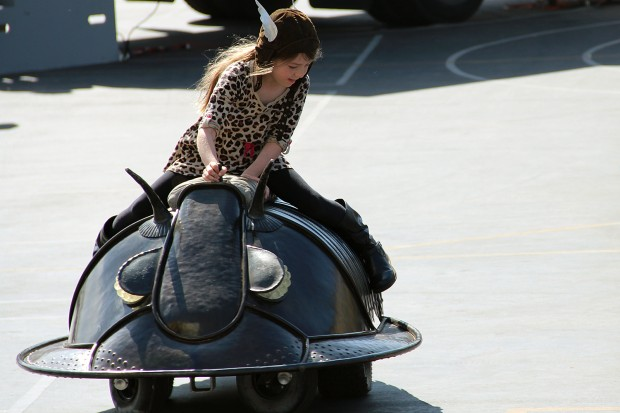 A girl rides a mechanical bug at On The Move at Buena Vista Horace Mann.