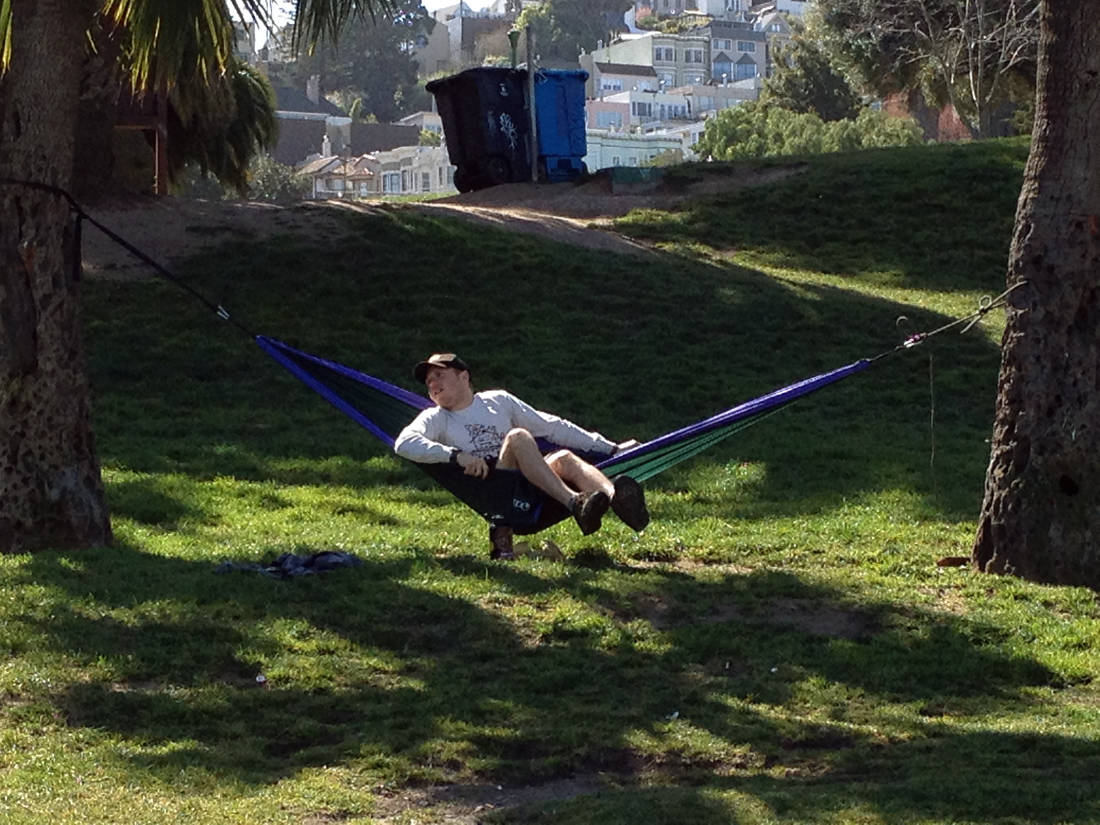 A person sits in a hammock in Dolores Park.