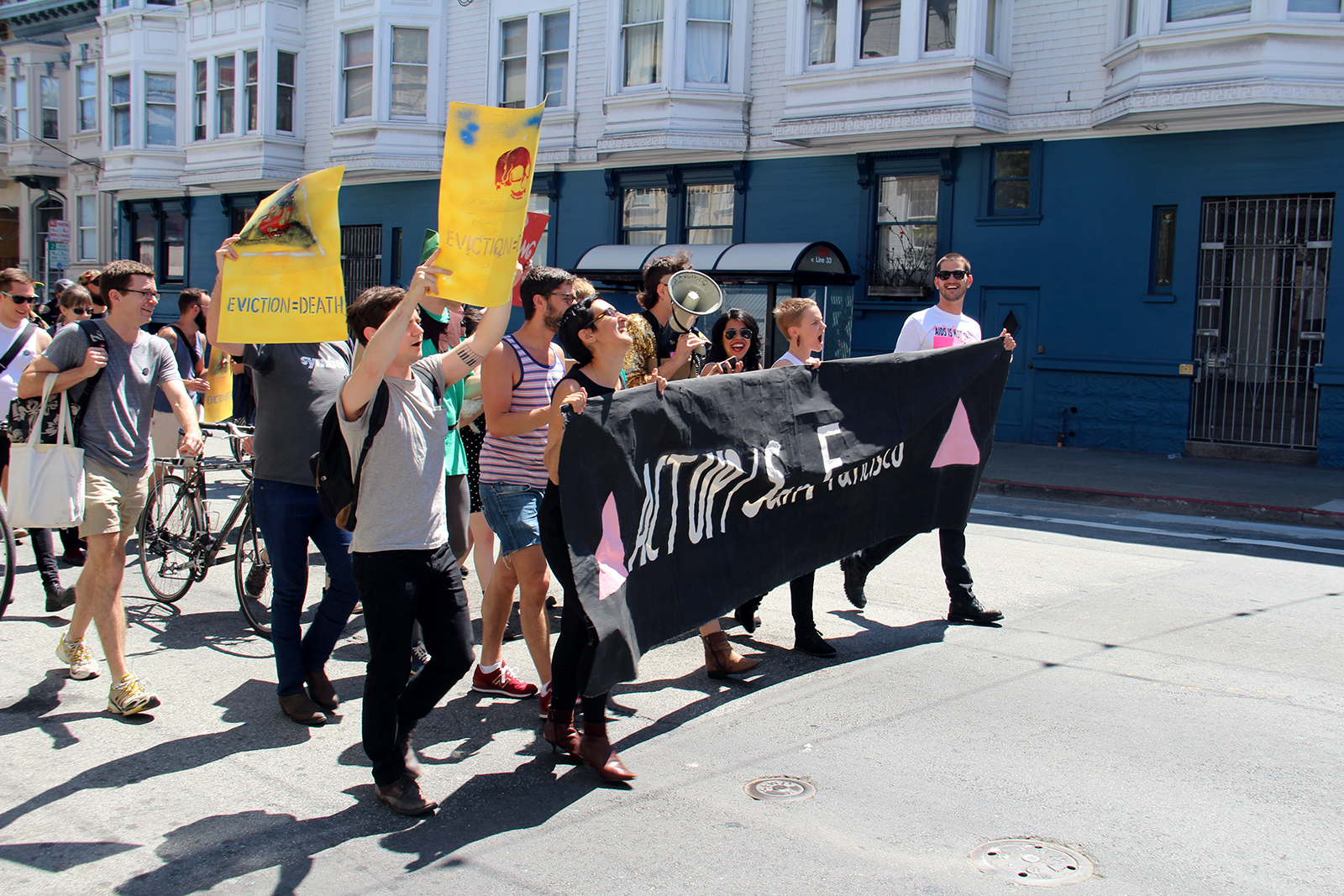 """A group of people protesting San Francisco evictions marches down 18th Street. """"Out of the bakery and into the streets,"""" they yell when they reach Tartine. Photo by Molly Oleson"""