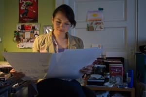 """Liz Mayorga looks at pages of """"Monstrous Love Stories"""" in her apartment in the Mission."""
