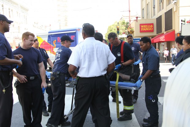 Law enforcement and medical officials assist a man who was partially run over at Mission and 22nd Streets, May 2, 2013.
