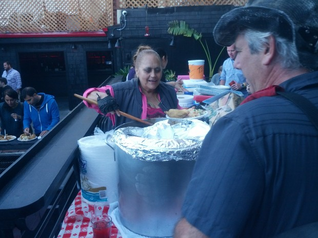 Virginia Ramos, aka the Tamale Lady, serves guests at her 60th birthday party at the Eagle Bar.
