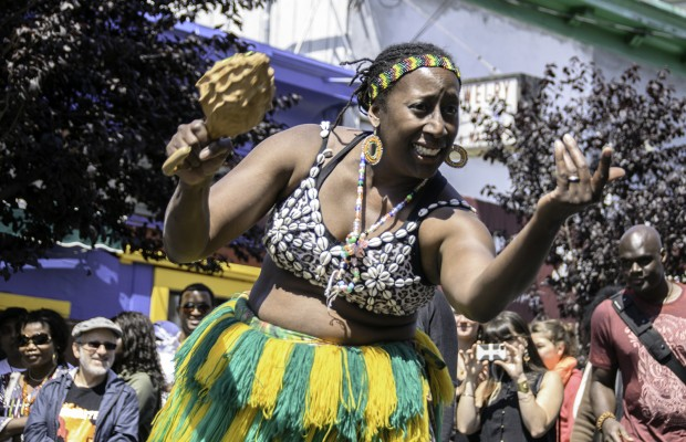 A dancer from the Chinyakare Ensemble of Zimbabwe beckons people in the crowd to join the dance.