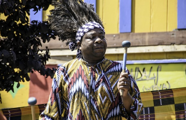 A drummer from the Chinyakare Ensemble of Zimbabwe accompanies the dancers.