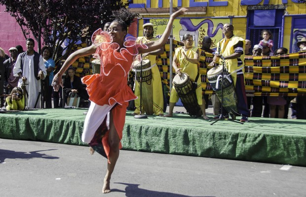 A member of the Musanga ensemble dances to the accompaniment of the drummers.
