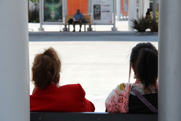 Two women wait for an AC Transit bus at the Temporary Transbay Terminal at Howard and Beale Streets.