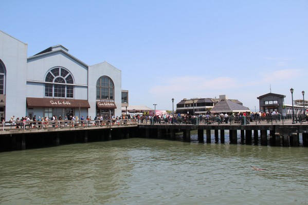 A long line of people waiting for a ferry to the East Bay winds around the docks in front of Pier 2 on the Embarcadero.