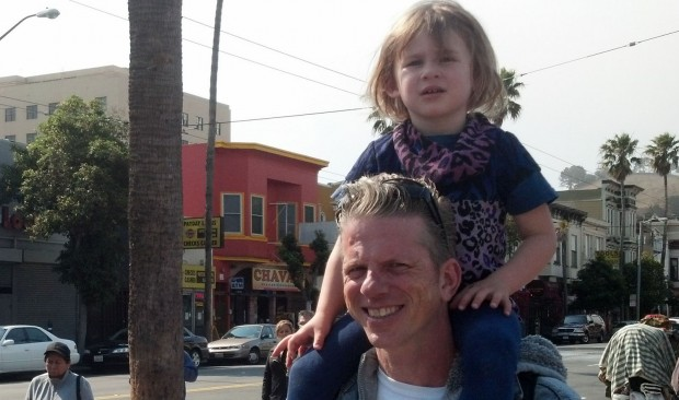 Hannah Iger, 3, sits on the shoulders of Johnny Lorenz at a 24th and Mission Street bus stop. Lorenz is waiting for the bus to take Iger to daycare.