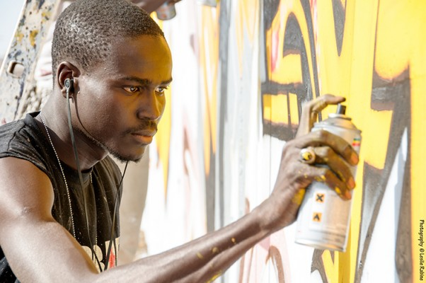 """Festigraff, Day 1: The HLM neighborhood. Artist Mad Zoo (Serigne Moumar Fall) works on a wall. The message for this wall is: """"Believe in yourself however long it takes, and you will have success."""""""